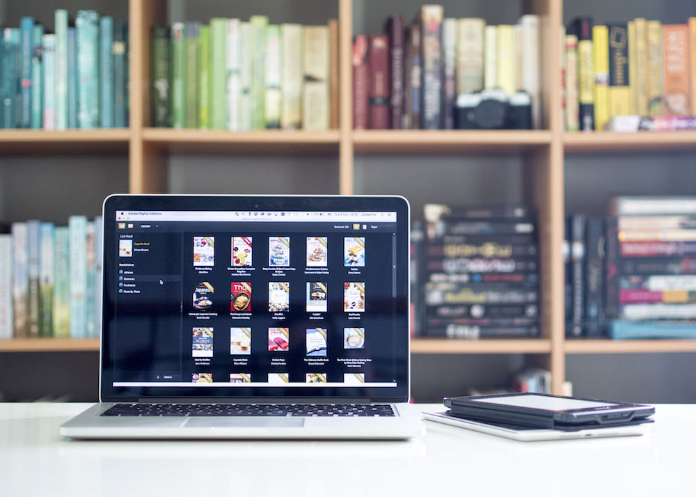 Adobe Digital Editions on a Mac in front of bookshelf