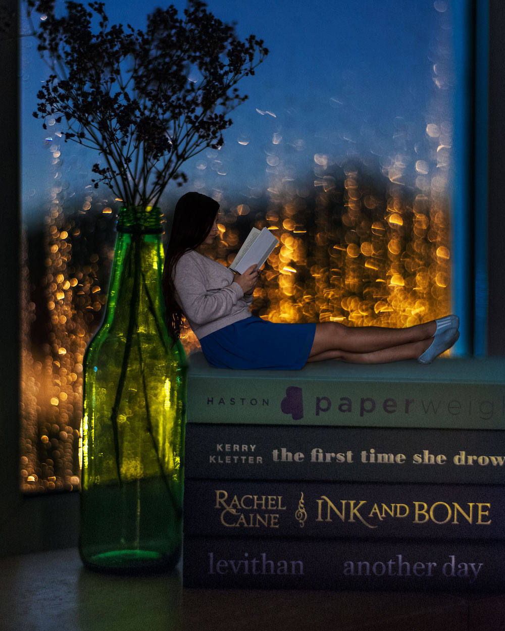 Bookish Scene: April Showers – sitting on a book stack by the window with rain bokeh