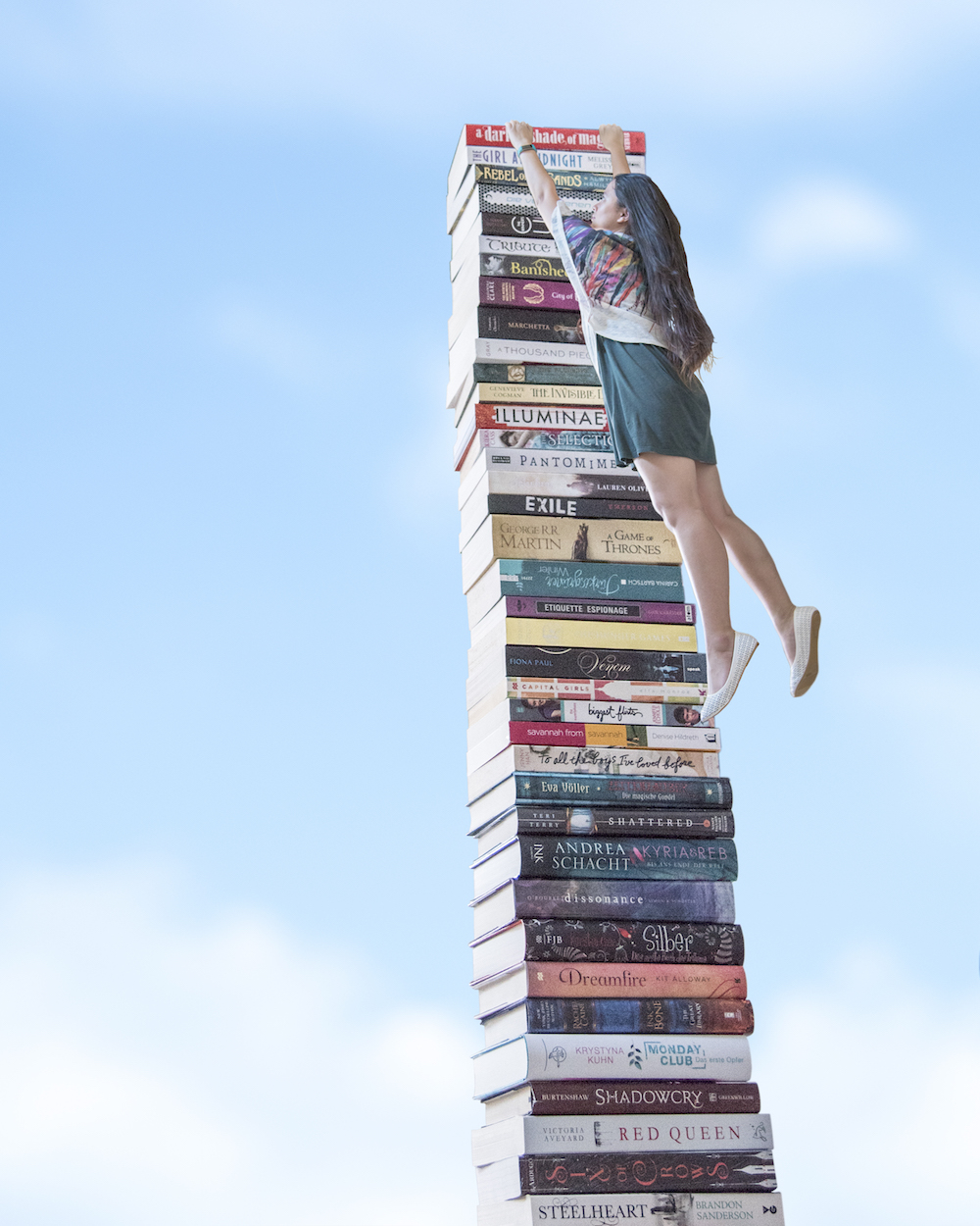 Bookish Scene: New Beginnings – Creative photography, hanging onto a tower of books