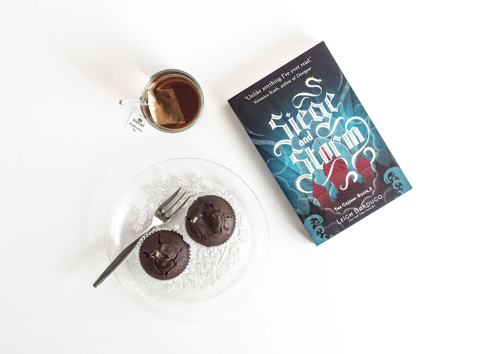 Photo of Siege and Storm with tea and cupcakes on white background to demonstrate clear book photography with a DSLR