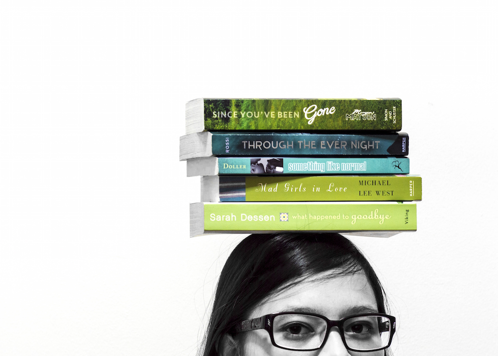 Wearing glasses while balancing a stack of green books on top of my head