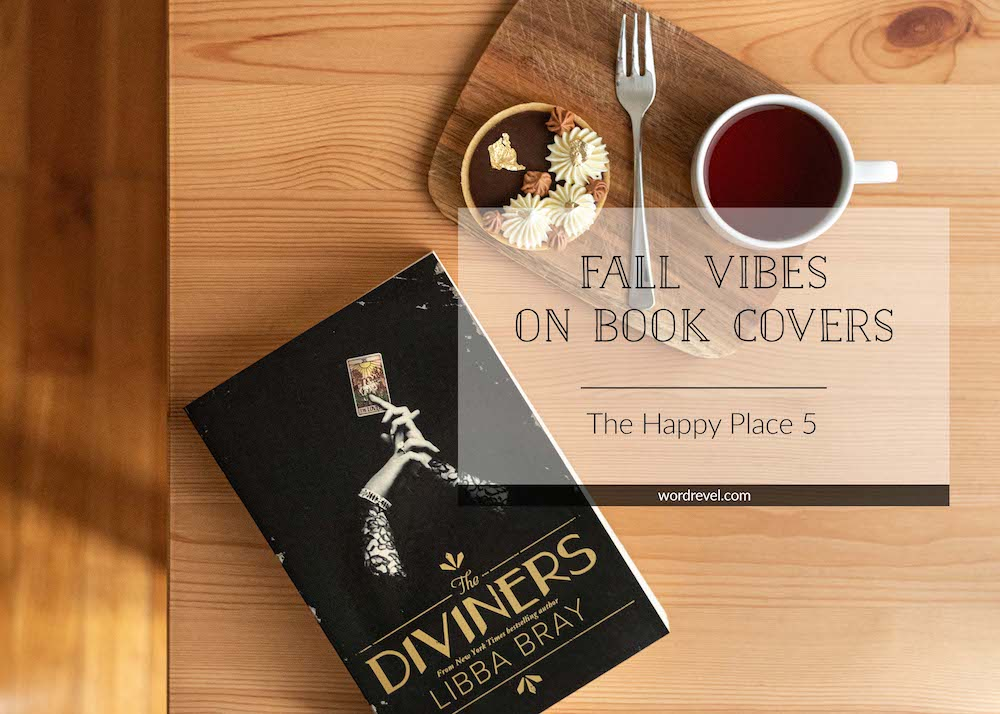 """Top down view on coffee table with Australian paperback of edition of The Diviners by Libba Bray placed on the left bottom corner. A small wooden board is beside the top right corner of the book. A Nutella chocolate tart, dessert fork and cup of tea are on the wooden board. The photo has a text box overlay with the post title, """"Fall Vibes on Book Covers, The Happy Place 5."""""""