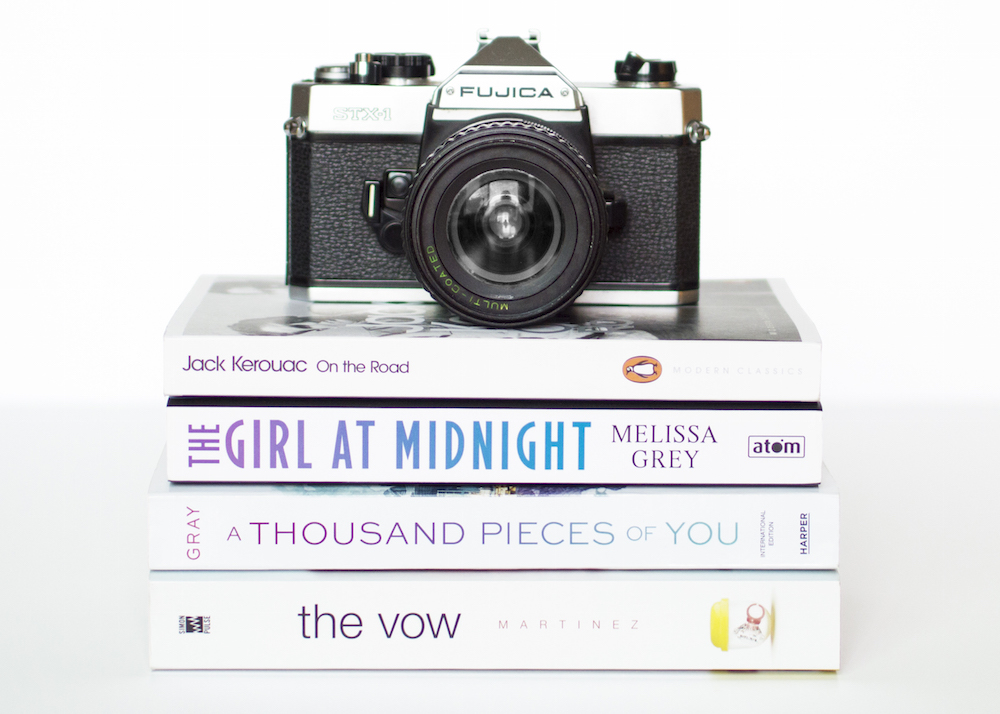 White stack of books with camera against stealing photos